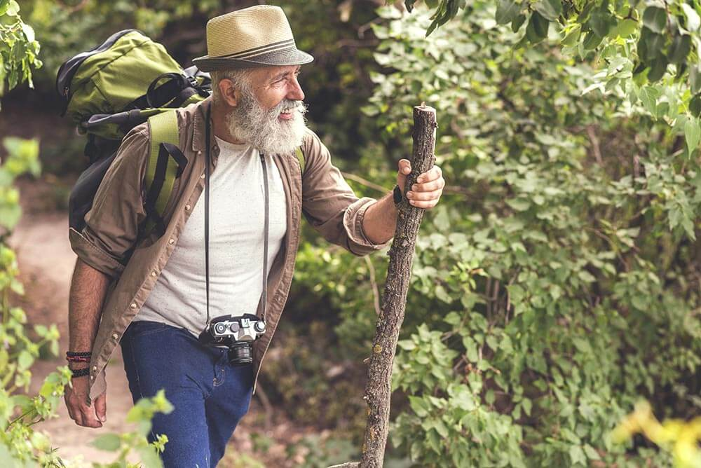 Older man hiking tin the woods