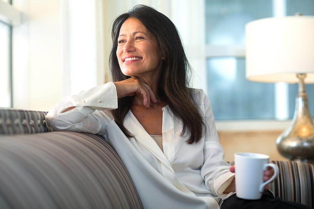 Woman enjoying coffee at home on a couch