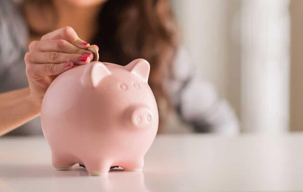 Woman dropping a coin into a piggybank
