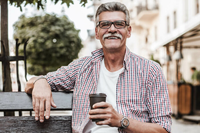 older man with mustache drinking coffee