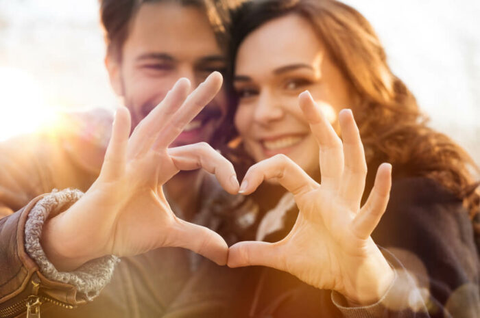 young couple making a heart with hands